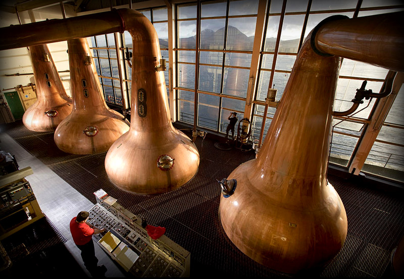 The still men at Caol Ila scotch whisky distillery, pause at dawn, to take in the view. Port Askaig, Isle of Islay, Scotland, UK 11/03/08